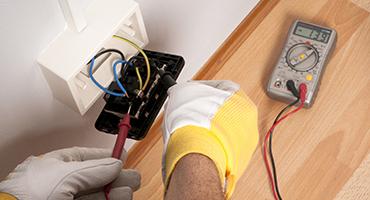 Eletricista medindo tensão de tomada